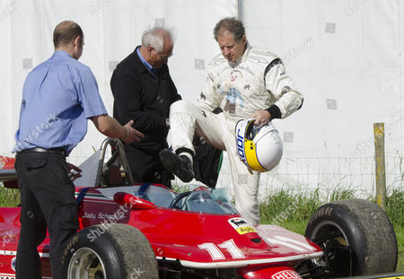 Jody Scheckter, former Formula One driving star, gets into a racing car he used to drive, at CarFest