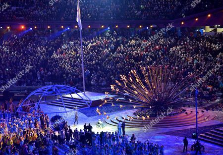 Numerous flames gradually form the Paralympic cauldron after it is lit by Margaret Maughan