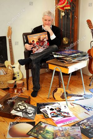 Portrait Of English Author Jonathan Coe Posing With His Collection Of Vinyl Records