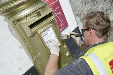 Glyn from Romec painting a Royal Mail post box gold in honour of Jonathan Fox's gold medal win at the London 2012 Paralympic Games