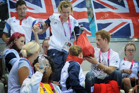 Prince Harry helps Team GB swimmer Hannah Russell to her seat when he visited the Aquatics Centre