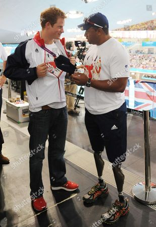 Prince Harry meets former soldier and Paralympic athlete Derek Derenalagi at a visit to the Aquatics Centre where he watched swimming heats with Team GB swimmers