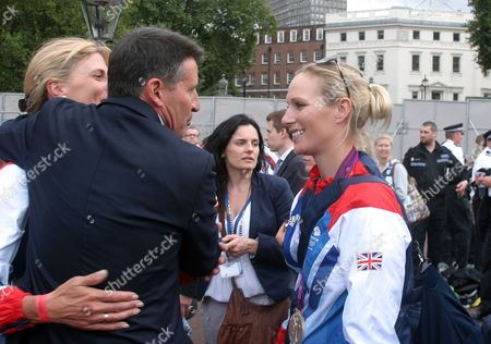 Kristina Cook gets a hug from Lord Sebastian Coe with Zara Phillips looking on, outside Buckingham Palace