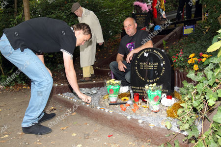 Fans light candles to remember glam rock legend Marc Bolan at the site of his death in a car crash