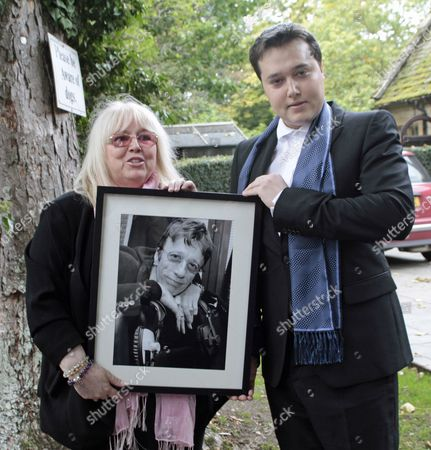 Dwina Gibb and Robin-John Gibb with a photo of Robin