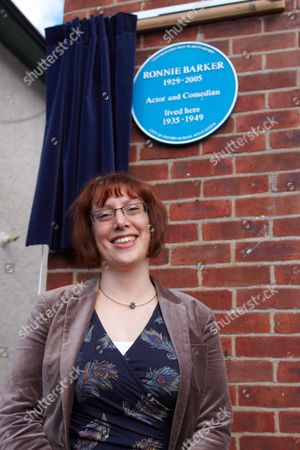 Stock Photo of Homeowner Dr Zena  Kamash poses in front of a blue plaque honouring Ronnie Barker on his former family home