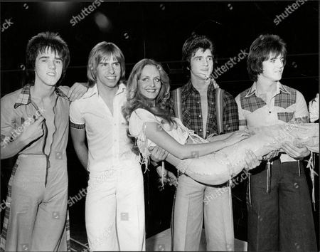 Stock Photo of Pop Group Bay City Rollers With Fashion Model Twiggy The Bay City Rollers Were A Scottish Pop Band Whose Popularity Was Highest In The 1970s. The British Hit Singles & Albums Noted That They Were 'tartan Teen Sensations From Edinburgh' And Were 'the First Of Many Acts Heralded As The 'biggest Group Since The Beatles' And One Of The Most Screamed-at Teeny-bopper Acts Of The 1970s'.[1] For A Relatively Brief But Fervent Period (nicknamed 'rollermania') They Were Worldwide Teen Idols. The Group's Line-up Featured Numerous Changes Over The Years But The Classic Line-up During Its Heyday Included Guitarists Eric Faulkner And Stuart Wood Singer Les Mckeown Bassist Alan Longmuir And Drummer Derek Longmuir.