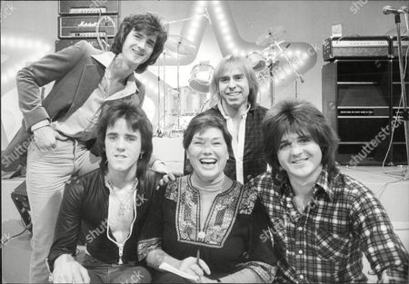 Stock Image of Pop Group Bay City Rollers With Television Presenter Murial Young The Bay City Rollers Were A Scottish Pop Band Whose Popularity Was Highest In The 1970s. The British Hit Singles & Albums Noted That They Were 'tartan Teen Sensations From Edinburgh' And Were 'the First Of Many Acts Heralded As The 'biggest Group Since The Beatles' And One Of The Most Screamed-at Teeny-bopper Acts Of The 1970s'.[1] For A Relatively Brief But Fervent Period (nicknamed 'rollermania') They Were Worldwide Teen Idols. The Group's Line-up Featured Numerous Changes Over The Years But The Classic Line-up During Its Heyday Included Guitarists Eric Faulkner And Stuart Wood Singer Les Mckeown Bassist Alan Longmuir And Drummer Derek Longmuir.