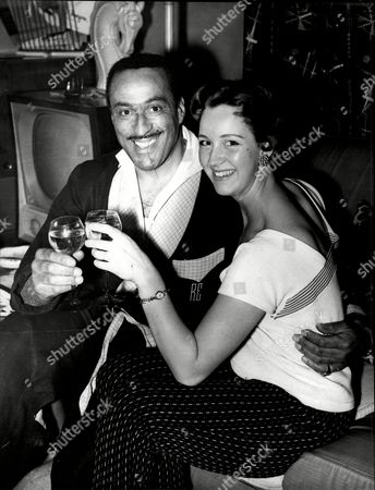 Singer And Bandleader Ray Ellington And Fiancee Later To Be His Wife Actress Anita West (ann Wuest) Henry Pitts Brown (17 March 1915 A 27 February 1985) Known Professionally As Ray Ellington Was A Popular English Singer Drummer And Bandleader. He Is Best Known For His Appearances On The Goon Show From 1951 To 1960. The Ray Ellington Quartet Had A Regular Musical Segment On The Show And Ellington Also Had A Small Speaking Role In Many Episodes Often As A Parodic African Native American Or Arab Chieftain (but Also Often With No Attempt To Change His Normal Accent As A Female Secretary Or A Scotsman). He Was Married To Anita West Who Was To Become The Second Female Presenter Of Blue Peter When She Replaced Leila Williams But She Only Lasted A Few Weeks In This Role. They Had Two Small Children (lance And Nina) When The Marriage Ended In Divorce Due To Ellington's Constant Touring. Ellington's Recording Of 'the Madison' Reached #36 In The Uk Singles Chart In November 1962. Ray's Son Lance Ellington Is A Singer Who Has Recorded Several Jazz Oriented Albums And Is One Of The Backing Singers In The Bbc Show Strictly Come Dancing. Lance Ellington Also Appeared In Tributes To Peter Sellers And In The Film The Life And Death Of Peter Sellers Where He Played His Father. Ray Ellington Died Of Cancer On 27 February 1985.
