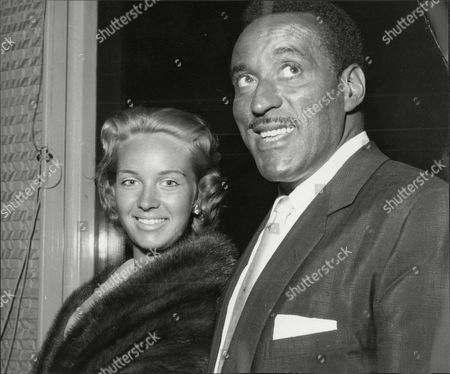 Singer And Bandleader Ray Ellington With Wife Actress Anita West (ann Wuest) At London Airport Henry Pitts Brown (17 March 1915 A 27 February 1985) Known Professionally As Ray Ellington Was A Popular English Singer Drummer And Bandleader. He Is Best Known For His Appearances On The Goon Show From 1951 To 1960. The Ray Ellington Quartet Had A Regular Musical Segment On The Show And Ellington Also Had A Small Speaking Role In Many Episodes Often As A Parodic African Native American Or Arab Chieftain (but Also Often With No Attempt To Change His Normal Accent As A Female Secretary Or A Scotsman). He Was Married To Anita West Who Was To Become The Second Female Presenter Of Blue Peter When She Replaced Leila Williams But She Only Lasted A Few Weeks In This Role. They Had Two Small Children (lance And Nina) When The Marriage Ended In Divorce Due To Ellington's Constant Touring. Ellington's Recording Of 'the Madison' Reached #36 In The Uk Singles Chart In November 1962. Ray's Son Lance Ellington Is A Singer Who Has Recorded Several Jazz Oriented Albums And Is One Of The Backing Singers In The Bbc Show Strictly Come Dancing. Lance Ellington Also Appeared In Tributes To Peter Sellers And In The Film The Life And Death Of Peter Sellers Where He Played His Father. Ray Ellington Died Of Cancer On 27 February 1985.