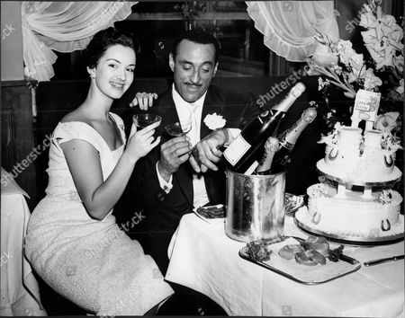 Singer And Bandleader Ray Ellington With Wife Actress Anita West (ann Wuest) At Their Wedding Reception Henry Pitts Brown (17 March 1915 A 27 February 1985) Known Professionally As Ray Ellington Was A Popular English Singer Drummer And Bandleader. He Is Best Known For His Appearances On The Goon Show From 1951 To 1960. The Ray Ellington Quartet Had A Regular Musical Segment On The Show And Ellington Also Had A Small Speaking Role In Many Episodes Often As A Parodic African Native American Or Arab Chieftain (but Also Often With No Attempt To Change His Normal Accent As A Female Secretary Or A Scotsman). He Was Married To Anita West (ann Wuest) Who Was To Become The Second Female Presenter Of Blue Peter When She Replaced Leila Williams But She Only Lasted A Few Weeks In This Role. They Had Two Small Children (lance And Nina) When The Marriage Ended In Divorce Due To Ellington's Constant Touring. Ellington's Recording Of 'the Madison' Reached #36 In The Uk Singles Chart In November 1962. Ray's Son Lance Ellington Is A Singer Who Has Recorded Several Jazz Oriented Albums And Is One Of The Backing Singers In The Bbc Show Strictly Come Dancing. Lance Ellington Also Appeared In Tributes To Peter Sellers And In The Film The Life And Death Of Peter Sellers Where He Played His Father. Ray Ellington Died Of Cancer On 27 February 1985.