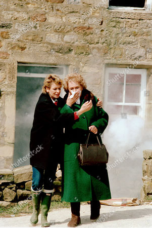 Stock Picture of Dolly Skilbeck [Jean Rogers] helps Annie Sugden [Sheila Mercer] away from the fire at Crosgill.