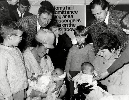 Stock Image of British Families Adopt Vietnamese Orphans - Scene At Heathrow Airport (r) Ralph Green And Wife Charmaine With Baby Emma (l) Adrian Wooldridge And Wife Pat With Baby Nicholas.