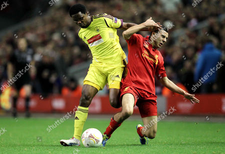 Samuel Eto'o of Anzhi Makhachkala receives a yellow card for this challenge on Oussama Assaidi of Liverpool