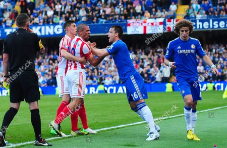 John Terry of Chelsea holds back an angry Jonathan Walters of Stoke City from confronting David Luiz after a foul by Luiz near the end