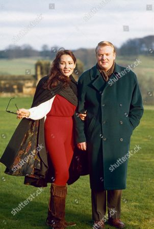BARBARA CARRERA AND THE DUKE OF NORTHUMBERLAND, HENRY PERCY WALKING ON HIS ESTATE ALNWICK CASTLE