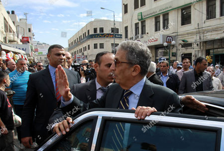 Egyptian politician and former Arab League Secretary-General, Amr Moussa waving to supporters as he walks around the old town market