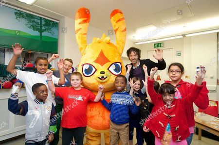 Moshi Monsters founder Michael Acton Smith with a Moshi character and a group of children at Great Ormond Street Hospital