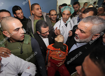 Egyptian Prime Minister Hesham Qandil and Palestinian Prime Minister in the Gaza Strip Ismail Haniyeh with the body of a young boy killed in an Israeli airstrike