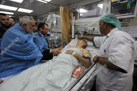 Egyptian Prime Minister Hesham Qandil and Palestinian Prime Minister in the Gaza Strip Ismail Haniyeh visit a casualty of the Israeli airstrikes in hospital