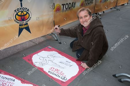 Artist Mark Kostabi makes a sign for the Today Show