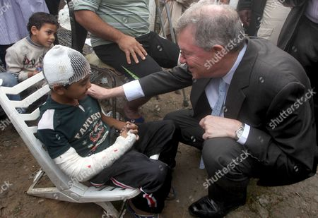Robert H. Serry, the United Nations special coordinator for the Middle East Peace Process, talks with a wounded Palestinian boy during his visit