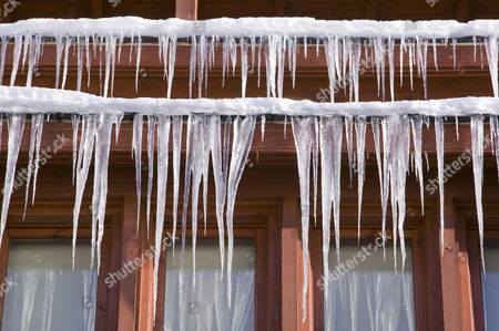 Stock Image of Icicles hanging from a chalet roof in the Andorran ski resort of Soldeu el Tarter