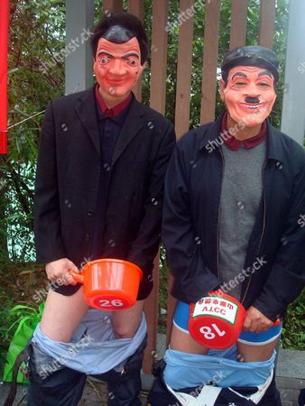 Masked men pretend to masturbate into buckets during the contest