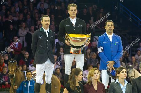 Marc Houtzager celebrates the first place next to Denis Lynch for the second place (L) and Alvaro Alfonso De Miranda Neto for the third place (R)