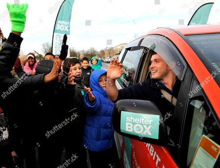Greeted by local school children Mike Perham arrives back at the RAF Museum in North London, after successfully circumnavigating the globe in a Spaceship Camper van