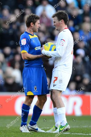 Stock Picture of Stacy Long of AFC Wimbledon and Stephen Gleeson of MK Dons all smiles after previously grappling for the ball