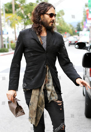 Russell Brand holding a bag from Louis Vuitton