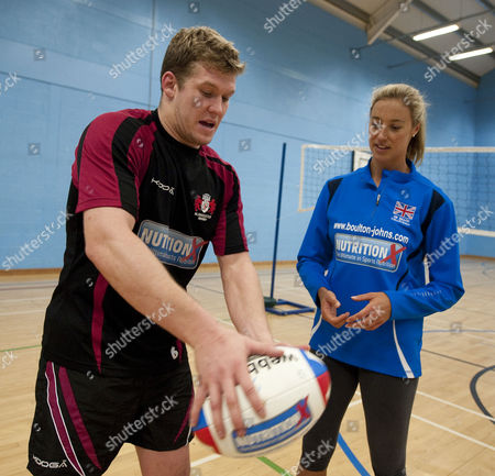 Stock Picture of Gloucester Rugby Player Luke Narroway Teaches 2012 Volleyball Player Denise Johns How To Spin Pass At Hartpury College Gloucester.