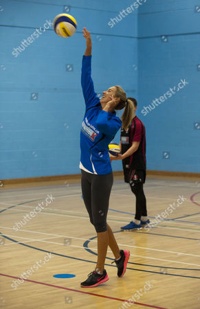 Volleyball Player Denise Johns Shows Gloucester Rugby Player Freddie Burns How To Serve In Volleyball At Hartpury College Gloucester.