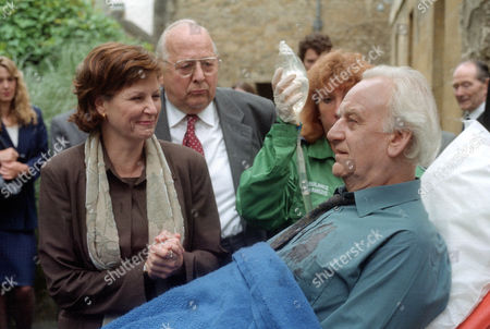 Lisa Eichhorn as Millie Van Bunnen and James Grout as Chief Supt. Strange look on in anguish as Inspector Morse (John Thaw) is put into an ambulance after collapsing