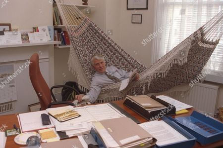Robin Hanbury-tenison Explorer And Chief Executive Of The British Field Sports Society At Their Kennington South London Hq Today Pix Include Him On His Southern American Hammock Behind His Desk As He Answers The Phone.