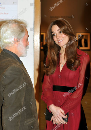 Catherine Duchess of Cambridge talks to artist Paul Emsley after viewing his new portrait of her