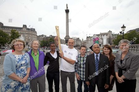 Olympic Possible Torch Bearers Hold A Replica Of The Olympic Torch Which Is On Tour Around London And The South East Vernon Udugampola - Asian Man In The Suit Sue Brooks - Short Lady In A Grey Suit Jacket Rosemary Chileshe - Tall Black Lady Andy Gibbs - Tall Man In White Help For Heroes T-shirt Anne Corbett - Short Lady In A Blue Flowery Dress Sarah-jo Mclellan - Lady In A Brown Dress Michael Horowitz - Older Man With Grey Hair In Purple Top Anton Haynes - Guy In Checked Green Shirt.