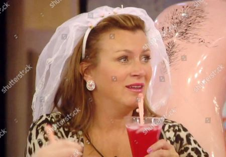 Tricia Penrose drinking a cocktail with a straw shaped like a penis
