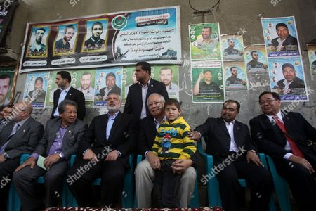 Malaysian Prime Minister Najib Tun Razak, hugs the son of late Hamas military commander Ahmed Al-Jaabari while he sits next to Ismail Haniyeh