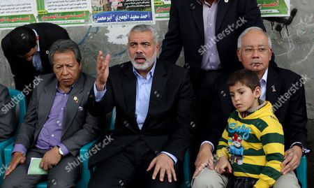 Stock Image of Malaysian Prime Minister Najib Tun Razak, hugs the son of late Hamas military commander Ahmed Al-Jaabari while he sits next to Ismail Haniyeh