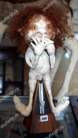 Lot 258 A Novelty Metronome Mounted With A Naked Harmonic Playing Troll At The Auction Of Property Owned By John Entwistle The Former Bass Guitarist With 'the Who' At Frogmill Hotel Andoversford Gloucestershire.