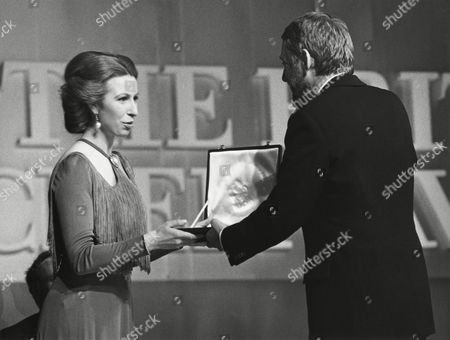 ROD MCEUEN accepting on behalf of JOHN WILLIAMS winner of the ANTHONY ASQUITH Award for JAWS and THE TOWERING INFERNO (1975) presented by HRH THE PRINCESS ANNE (PRESIDENT OF THE SFTA) at the Awards Ceremony in 1976