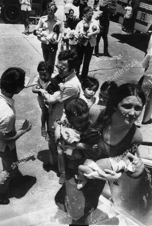 Vietnamese Orphans Board Our Aircraft At Tan Son Nhut Air Base. Operation Mercy Airlift - Chartered By The Daily Mail Brian Freemantle Daily Mail Journalist Is Centre Holding Child And Looking Left.