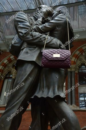 Embracing couple sculpture with Jack French handbag