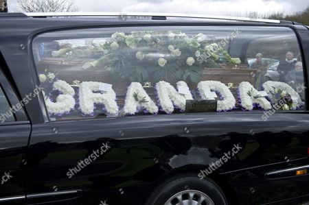 Hearse carrying Reg Presley's coffin with a floral wreath reading 'Grandad'