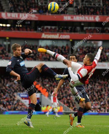 Alex Oxlade-Chamberlain of Arsenal attempts an overhead kick but it blocked by Morten Gamst Pedersen of Blackburn Rovers