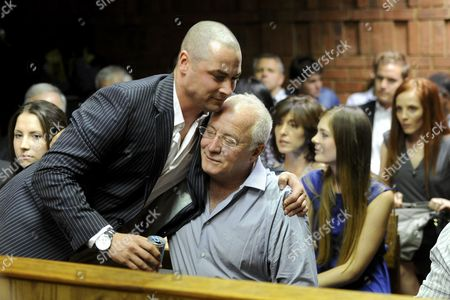 Oscar Pistorius's brother, Carl Pistorius, comforts their father, Henke Pistorius, during Oscar's bail hearing in the Pretoria Magistrate Court