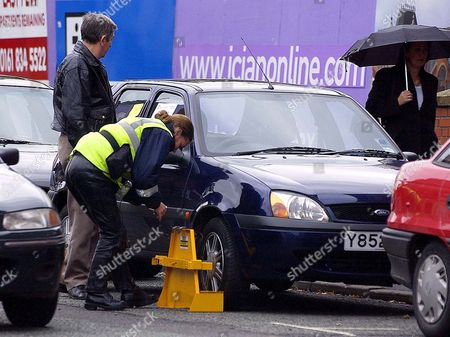 Stock Photo of Traffic Wardens Issue Internal Leaflet About Manchester Car Parking Hot Spots - On 'shudehill' Fiesta Car Owner Philip Stone Watches As His Car Is Unclamped By The Warden After Paying His Fine Even Though He Was Displaying A Disabled Badge In His Window And Parking Legally.