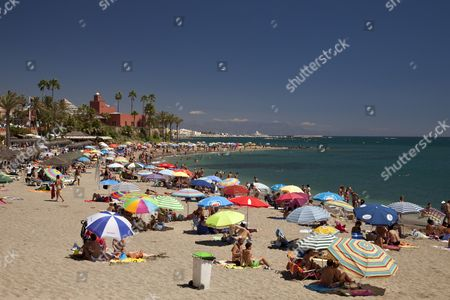 The busy Playa de Santa Ana beach and Castillo El Bil-Bil castle, Benalmadena, Malaga province, Costa del Sol, Andalusia, Spain